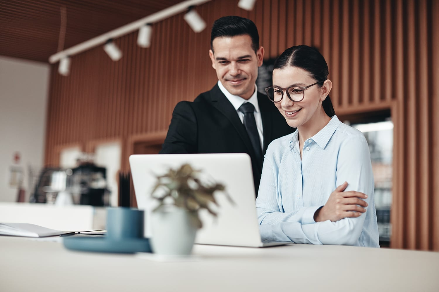 Two young businesspeople smiling while standing at a table going over notes and working on a laptop in an office